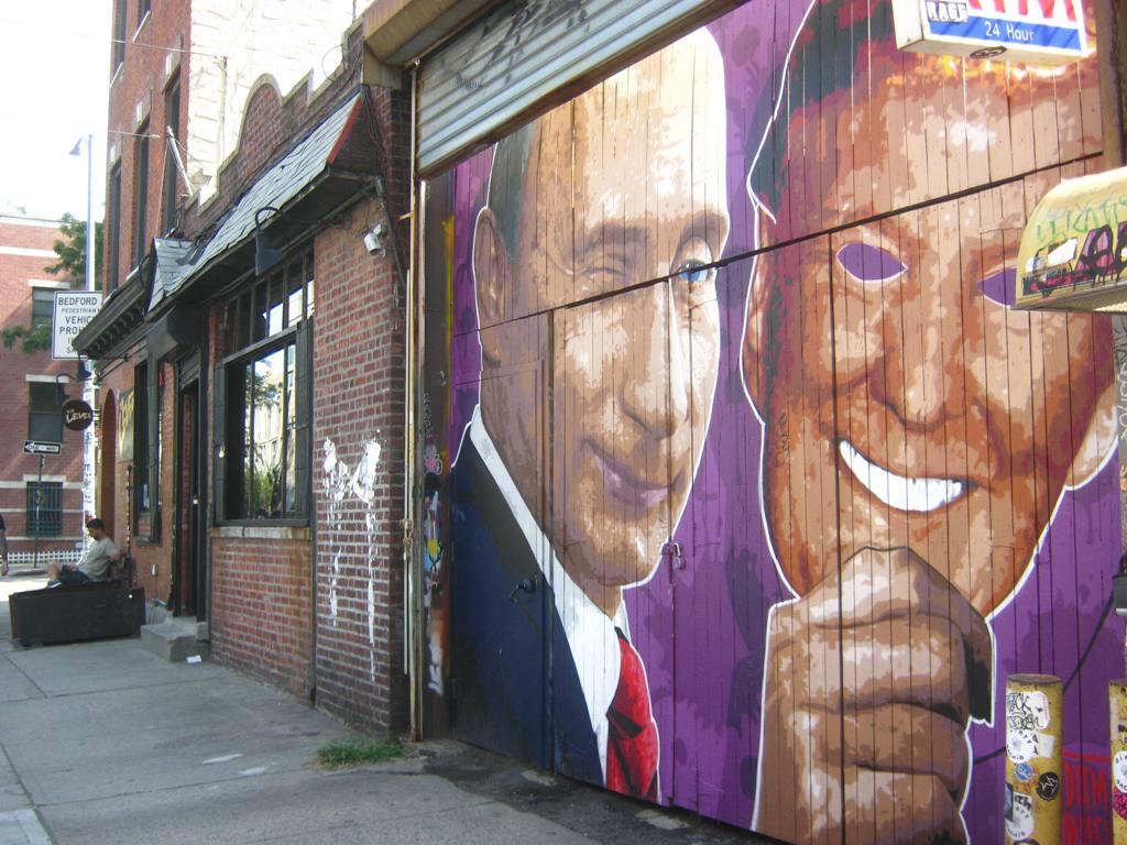 トランプ米大統領の仮面を脱ぐプーチン露大統領の壁画。風刺画。
