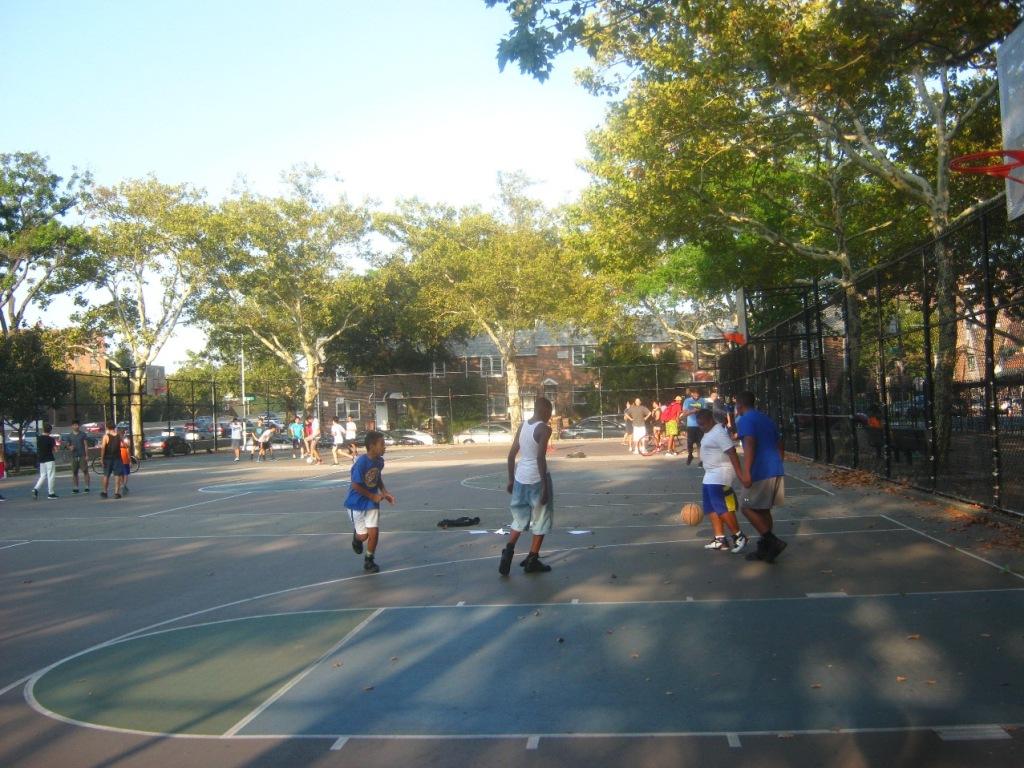 公園のバスケコートで少年たちがバスケットボール。